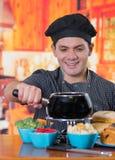 Przystojny uśmiechnięty młody cheff przygotowywa wyśmienitego Szwajcarskiego fondue gościa restauracji z asortowanymi serami i go Zdjęcie Stock