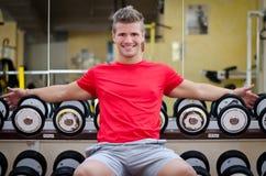 Przystojny uśmiechnięty młody człowiek w gym obsiadaniu na dumbbells dręczy Fotografia Stock