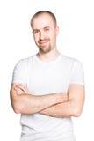 Przystojny uśmiechnięty młody człowiek z fałdowymi rękami w białej koszulce Fotografia Royalty Free