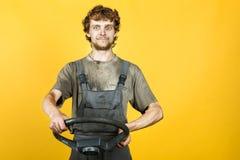 Przystojny uśmiechnięty mechanik utrzymuje koło żółty obrazy royalty free