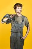 Przystojny uśmiechnięty mechanik z koła żółtym vertical zdjęcia royalty free