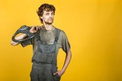 Przystojny uśmiechnięty mechanik z koło kolorem żółtym obraz royalty free