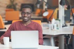 Przystojny uśmiechnięty pomyślny amerykanina afrykańskiego pochodzenia mężczyzna używa laptop obraz stock