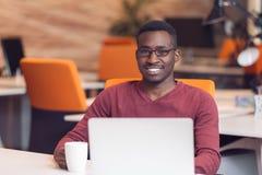 Przystojny uśmiechnięty pomyślny amerykanina afrykańskiego pochodzenia mężczyzna używa laptop fotografia royalty free