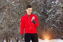 Przystojny uśmiechnięty sportowiec w czerwonym pulowerze używać jego li i telefon Obraz Stock