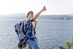 Przystojny uśmiechnięty wycieczkowicza facet bierze selfie fotografię zdjęcia royalty free