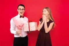 Przystojny uczeń, jest ubranym szkła, daje prezentowi i bukietowi kwiaty jego dziewczyna przeciw czerwonemu tłu obraz stock