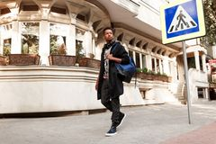 Przystojny ucze? na zewn?trz odprowadzenia na ulicie, w przypadkowych ubraniach z plecakiem i s?uchawki, blisko crosswalk, kopii  zdjęcia stock