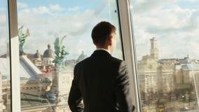 Przystojny ufny mężczyzna w czarnej kostium pozyci przeciw szklanej ścianie w kawiarni Zadziwiać Lviv sityscape na tle zbiory