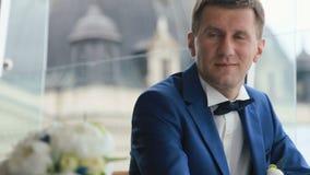 Przystojny ufny mężczyzna w czarnej kostium pozyci przeciw szklanej ścianie w kawiarni Zadziwiać Lviv sityscape na tle zdjęcie wideo