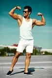 Przystojny umięśniony wzorcowy mężczyzna w przypadkowym płótnie w okularach przeciwsłonecznych w ulicie pokazuje jego mięśnie Zdjęcie Stock