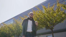 Przystojny urzędnik trzyma torby pić kawowy w ranku przed pracą blisko biura w kostiumu z szalikiem zdjęcie wideo