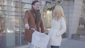 Przystojny wysoki mężczyzna trzyma jego bicykl opowiada z ładną blond kobietą w ciepłej kurtce Pozytywna pary gawędzenia pozycja zbiory