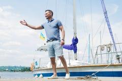 Przystojny yachtsman odprowadzenie przy rzecznymi mola i powitań gościami Młody biznesmen zaprasza jego łódź dla jacht przygody obraz stock
