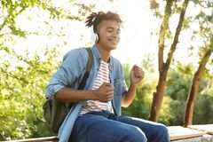 Przystojny z podnieceniem młody afrykański facet outdoors słucha muzykę z hełmofonami w parku zdjęcie royalty free