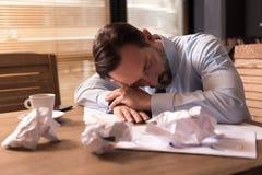 Przystojny zmęczony mężczyzna dosypianie przy miejscem pracy Zdjęcie Royalty Free