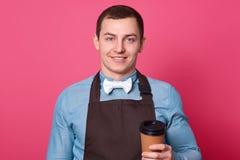 Przystojnych męskich kelnerów chwytów takeaway kawa jest ubranym koszula z bowtie, fartuch, chwyt papierowa napój filiżanka, posi zdjęcie stock