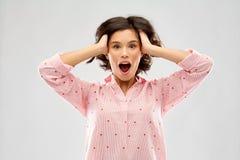Przytłaczająca młoda kobieta w piżamy mieniu przewodzić zdjęcia royalty free