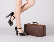 Pés da menina com uma mala de viagem. Foto de Stock Royalty Free