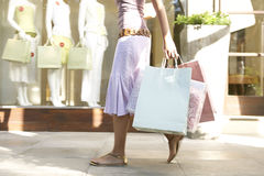 Pés da mulher com compra Imagens de Stock