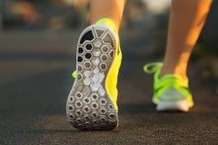 Pés da mulher do corredor que correm no close up da estrada na sapata Fitnes fêmeas Fotografia de Stock