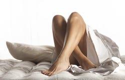 Pés da mulher na cama Fotografia de Stock Royalty Free