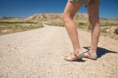 Pés da mulher na estrada do deserto Fotografia de Stock Royalty Free