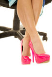 Pés da mulher nos saltos cor-de-rosa e nos pés de assento do vestido azul cruzados Imagem de Stock