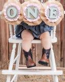 Pés das meninas do bebê de um ano com botas da vaqueira em uma cadeira alta Foto de Stock Royalty Free