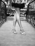 Pés das meninas na ponte em preto e branco Foto de Stock