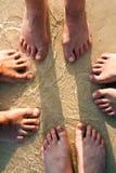 Pés de uma família na areia fina da praia Fotografia de Stock Royalty Free