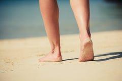 Pés de uma jovem mulher que anda na praia Fotografia de Stock