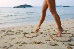 Pés de Womans na praia Foto de Stock