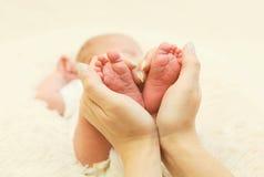 Pés do bebê na casa do close up do coração da forma Imagens de Stock