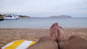 Pés do homem que encontram-se no vadio de Sun da praia perto do mar vídeos de arquivo