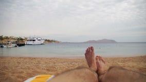 Pés do homem que encontram-se no vadio de Sun da praia perto do mar video estoque