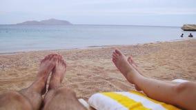 Pés dos povos que encontram-se no vadio de Sun da praia perto do mar video estoque
