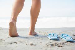 Pés fêmeas que pisam na areia ao lado dos falhanços de aleta Fotos de Stock