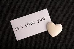 PS. I Love You. Handwritten on a white card with a cream colored heart symbolic of love and romance lying on a black background for a Valentines or anniversary Stock Photos