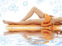 Pés longos da menina com a toalha alaranjada na areia branca Fotos de Stock Royalty Free