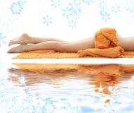 Pés longos de senhora relaxed com toalha alaranjada Fotos de Stock