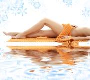 Pés longos de senhora relaxed com toalha alaranjada Foto de Stock