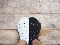 Pés que vestem peúgas preto e branco do às bolinhas Imagens de Stock