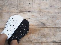 Pés que vestem peúgas preto e branco do às bolinhas Fotos de Stock Royalty Free