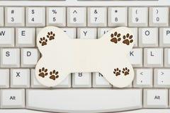 Psia kość z łapa drukami na klawiaturze fotografia stock