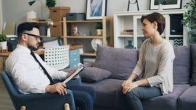 Psicólogo bem sucedido que dá o conselho à jovem mulher triste que fala no escritório video estoque