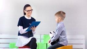 Psicólogo da criança fêmea que faz o apoio que discute com o rapaz pequeno na sessão de terapia vídeos de arquivo