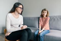 Psicólogo de sexo femenino joven que habla con la muchacha paciente del niño en oficina Salud mental de niños fotografía de archivo libre de regalías