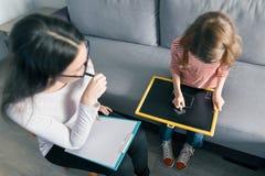 Psicólogo de sexo femenino joven que habla con la muchacha paciente del niño en oficina Salud mental de niños imagen de archivo