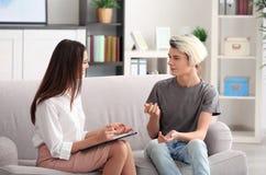 Psicólogo de sexo femenino joven que trabaja con el adolescente en oficina Fotos de archivo